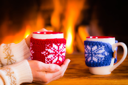 christmas tea: Woman hands holding Christmas cup near fireplace. Winter holiday concept