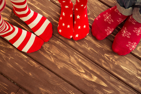 Feet wearing Christmas socks on wood floor. Happy family at home. Xmas holidays concept