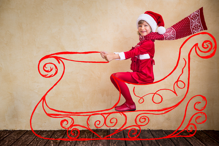 Happy kid drive in imaginary Santa Claus sleigh. Christmas miracle concept Stock Photo