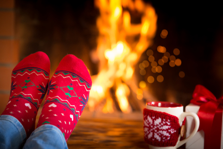 snug: Woman at home. Feet in Christmas socks near fireplace. Relaxing and comfort. Winter holiday concept