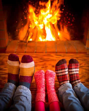 Familie zu Hause entspannen. Füße in Weihnachten Socken in der Nähe Kamin. Winter Urlaub Konzept Lizenzfreie Bilder