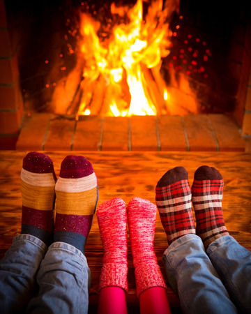 relaxation: Family relaxing at home. Feet in Christmas socks near fireplace. Winter holiday concept