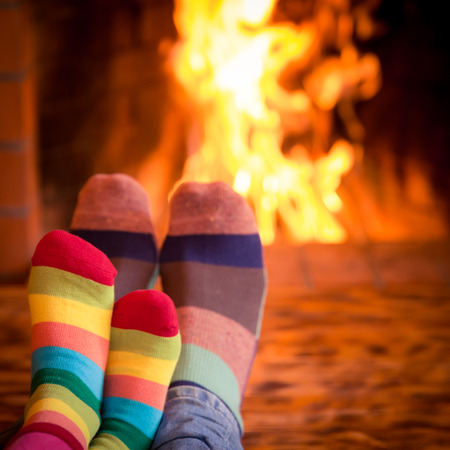 Father and kid's feet in Christmas socks near fireplace. Family relaxing at home. Winter holiday concept Stock Photo