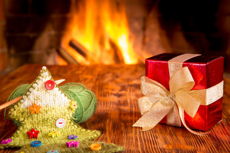 hearth and home: Christmas gift box on wood table against fireplace. Winter holiday concept