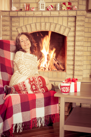 winter holiday: Woman relaxing at home near fireplace. Winter holiday concept