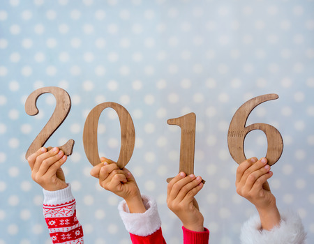 child: Happy New Year. Children hands holding wooden numbers 2016 against blue polka dot background. Winter holidays concept