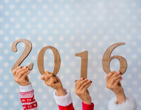 nowy rok: Szczęśliwego Nowego Roku. Ręce dzieci gospodarstwa numery drewniane 2016 na niebieskim tle polka dot. Zimowe wakacje koncepcji Zdjęcie Seryjne