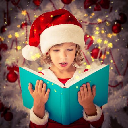 sorprendido: Niño sorprendido abriendo libro mágico de Navidad. Concepto de vacaciones de Navidad