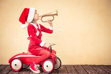 carritos de juguete: Niño a caballo en coche rojo de Navidad. Concepto de vacaciones de Navidad Foto de archivo