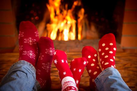 家族は、家でのんびり。暖炉の近くのクリスマスの靴下の中の足。冬の休日の概念