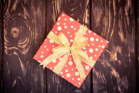 xmas background: Christmas gift box on wood background. Xmas holiday concept