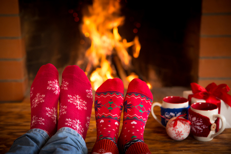 Couple relaxing at home. Feet in Christmas socks near fireplace. Winter holiday concept 스톡 콘텐츠