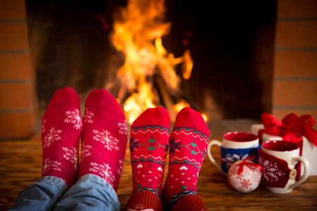 jolie pieds: Couple de d�tente � la maison. Les pieds dans des chaussettes de No�l pr�s de chemin�e. Concept de vacances d'hiver
