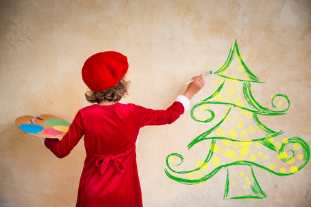 light painting: Child painting Christmas decorations. Kid playing at home. Xmas holiday concept