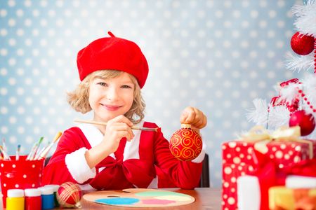 play room: Child painting Christmas decorations. Kid playing at home. Xmas holiday concept