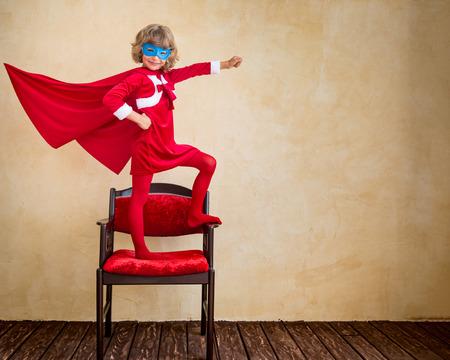 boy jumping: Chico super h�roe en casa. Concepto de vacaciones de Navidad