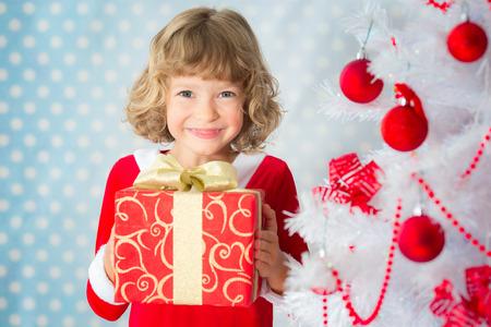 niños sonriendo: Niño que juega en casa. Árbol de Navidad. Concepto de vacaciones de Navidad