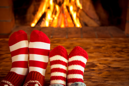 クリスマス ソックス暖炉の近くで母と子の足。人は自宅でリラックスします。冬の休日の概念