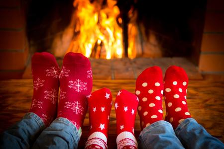 Familj avkopplande hemma. Fötter i julen strumpor i närheten av spisen. Vintersemester koncept