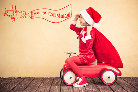 Child riding in red car. Kid holding Christmas bag. Xmas holiday concept Stock Photo
