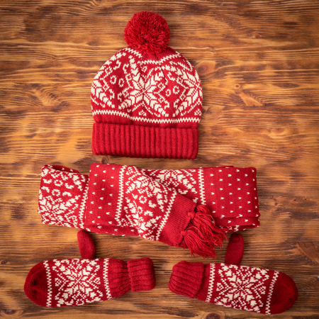ropa casual: ropa de invierno set - gorro de lana; bufanda y guantes en el fondo de madera Foto de archivo