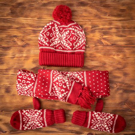 Winterkleidung eingestellt - Wollmütze; Schal und Handschuhe auf Holz Hintergrund