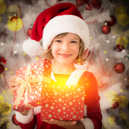 baby open present: Happy child opening magic Christmas gift box. Xmas holiday concept