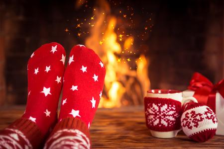 Frau zu Hause. Füße in Weihnachten Socken in der Nähe Kamin. Entspannend und Komfort. Winter Urlaub Konzept