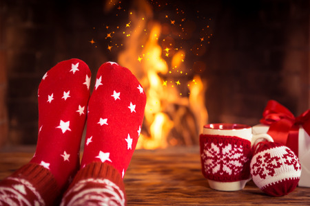 Woman at home. Feet in Christmas socks near fireplace. Relaxing and comfort. Winter holiday concept