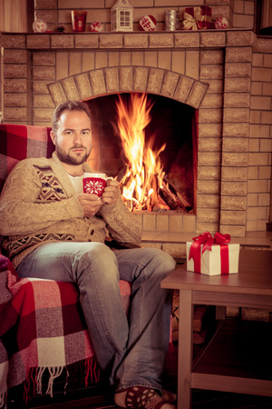 warm drink: Man relaxing at home near fireplace. Winter holiday concept