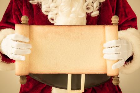 papier a lettre: Père Noël tenant papier parchemin vierge dans les mains. Concept de vacances de Noël