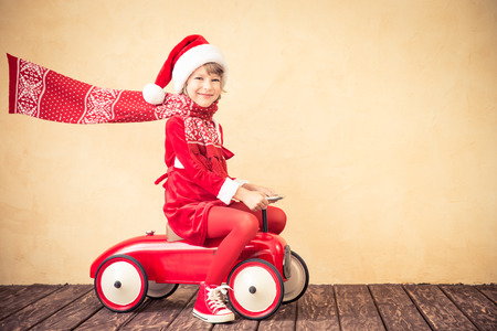 concept car: Child riding in red Christmas car. Xmas holiday concept