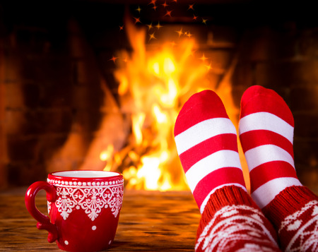 socks: Woman at home. Feet in Christmas socks near fireplace. Relaxing and comfort. Winter holiday concept