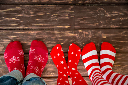 christmas sock: Feet wearing Christmas socks on wood floor. Happy family at home. Xmas holidays concept