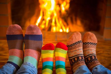 familj: Familj avkopplande hemma. Fötter i julen strumpor i närheten av spisen. Vintersemester koncept