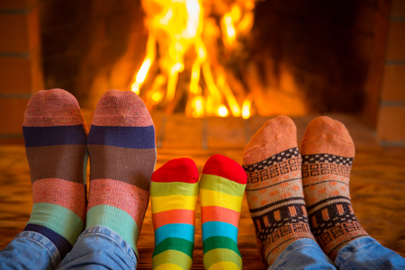relaxing: Family relaxing at home. Feet in Christmas socks near fireplace. Winter holiday concept