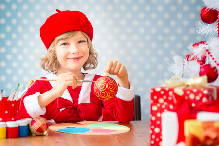 decorating christmas tree: Child painting Christmas decorations. Kid playing at home. Xmas holiday concept