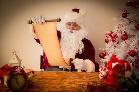 scroll: Santa Claus reading scroll. Christmas holiday concept Stock Photo