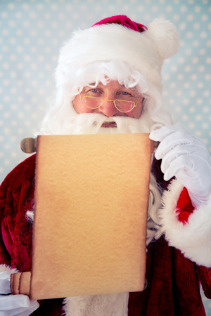 santa claus: Pap� Noel que sostiene el papel en blanco pergamino en las manos. Concepto de vacaciones de Navidad