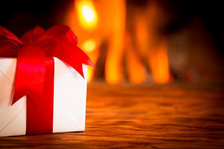 camino natale: Confezione regalo di Natale su tavola di legno contro il camino. Inverno concetto di vacanza