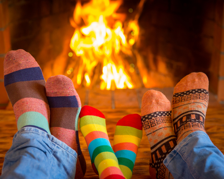 fireplace family: Family relaxing at home. Feet in Christmas socks near fireplace. Winter holiday concept