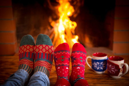 fireplace christmas: Couple relaxing at home. Feet in Christmas socks near fireplace. Winter holiday concept Stock Photo