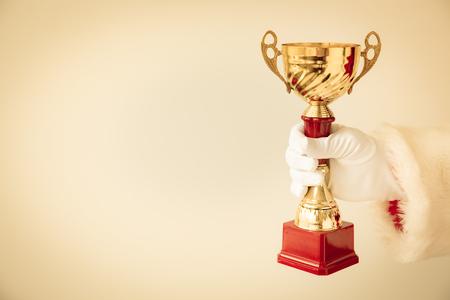 trofeo: Santa Claus sosteniendo trofeo de oro en las manos. Concepto de vacaciones de Navidad