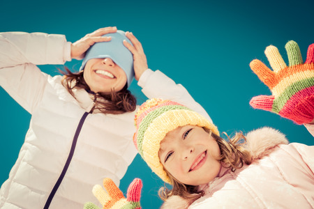 Glückliche Familie Spaß im Freien im Winter gegen blauen Himmel Hintergrund