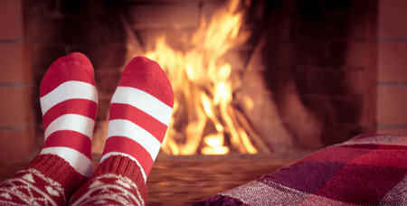 fireplace: Woman at home. Feet in Christmas socks near fireplace. Relaxing and comfort. Winter holiday concept