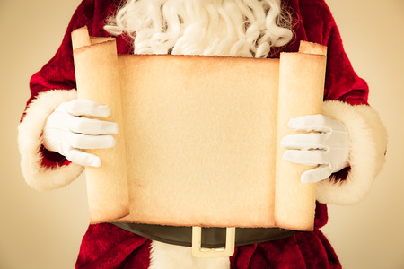 holding a christmas ornament: Santa Claus holding scroll paper blank in hands. Christmas holiday concept