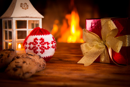 winter holiday: Christmas decorations on wood table near fireplace.  Winter holiday concept Stock Photo