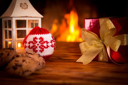 camino natale: Decorazioni di Natale su tavola di legno vicino al camino. Inverno concetto di vacanza