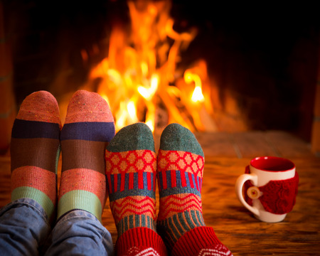 Couple relaxing at home. Feet in Christmas socks near fireplace. Winter holiday concept 免版税图像