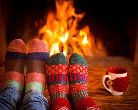 Paar ontspannen thuis. Voeten in sokken van Kerstmis dichtbij open haard. Winter concept vakantie